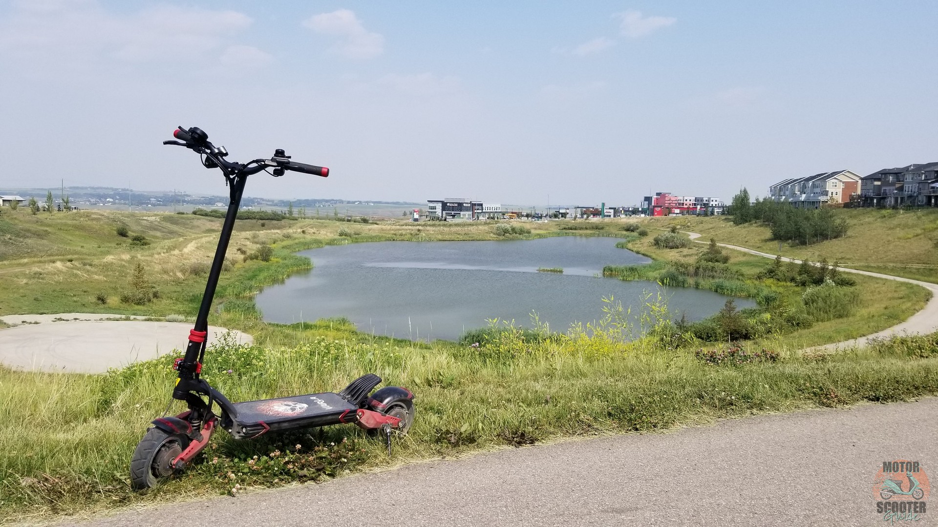 Eagle One scooter parked on side of a walking path with lake in background