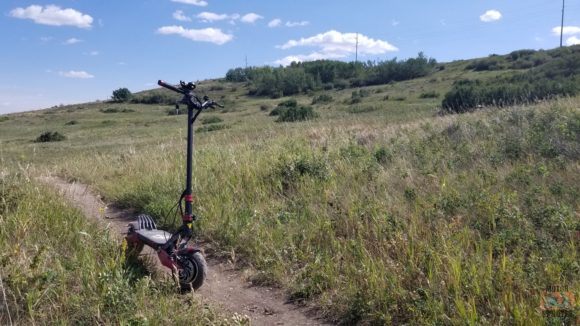 Eagle One scooter parked on side of Nose Hill Park dirt path