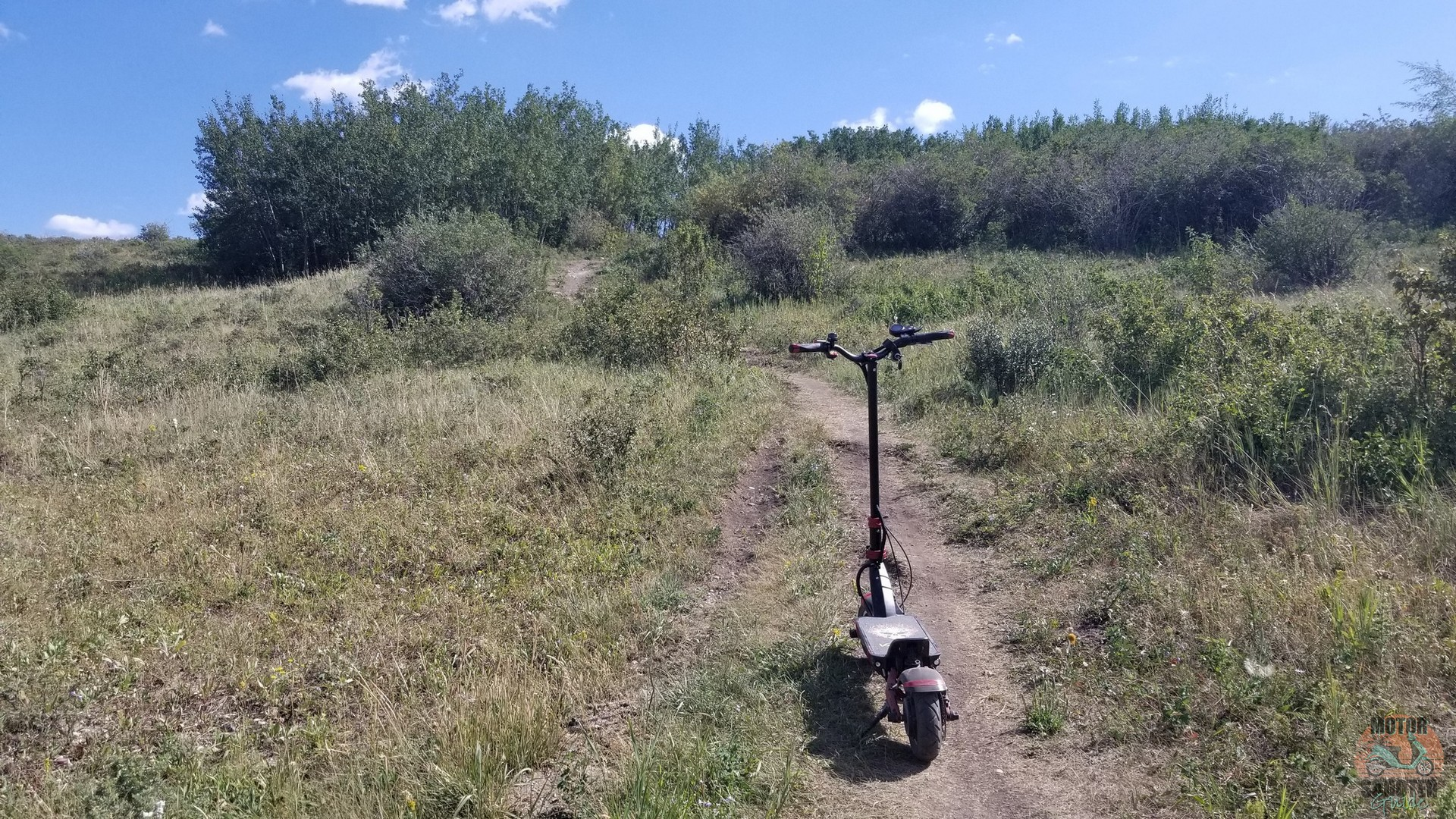 Eagle One scooter making its way up a dirt path incline at Nose Hill Park
