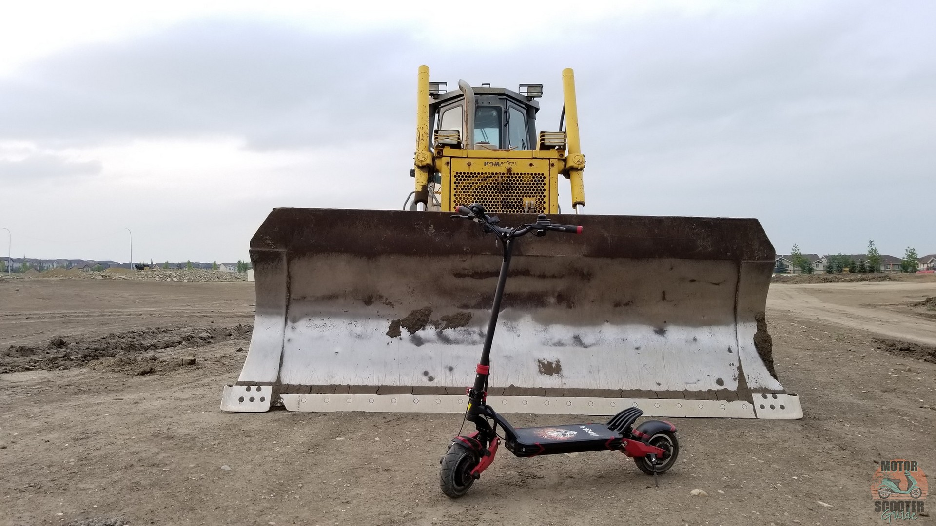 Eagle One scooter parked in front of a bulldozer